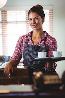 Kelnerka trzyma kawę