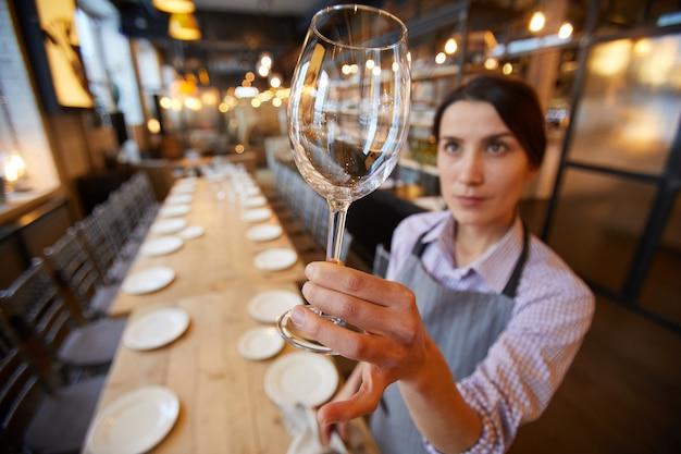 Kelnerka trzyma kryształowy kieliszek do wina