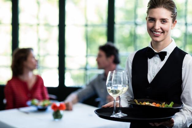 Kelnerka trzyma posiłek i kieliszki do wina w restauracji