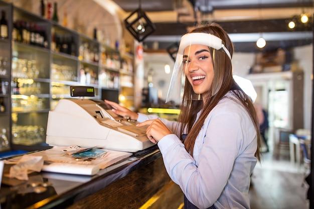 Kelnerka ubrana w fartuch, stojąca przy terminalu w punkcie sprzedaży i śmiejąca się podczas pracy w restauracji. piękna kobieta nosi osłonę twarzy podczas pandemii koronawirusa stojącej przy kasie