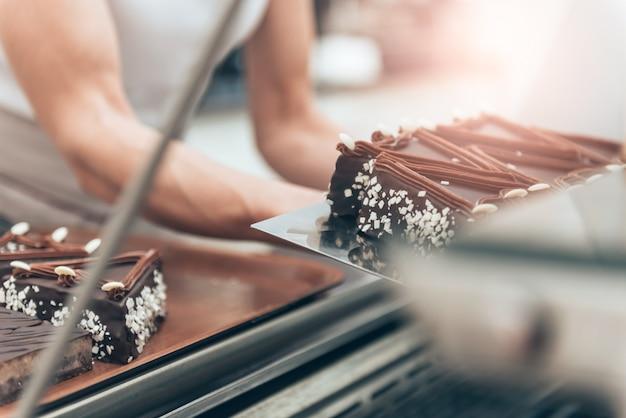 Kelnerka układa ciasto w gablocie