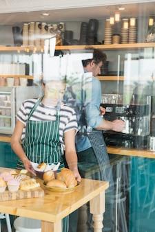 Kelnerka układa deser i przekąskę na ladzie, podczas gdy kelner przygotowuje kawę