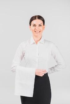 Kelnerka uśmiecha się i trzyma rękę za plecami