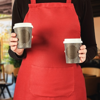 Kelnerka w fartuchu serwuje dwa papierowe kubki gorącej kawy na wynos