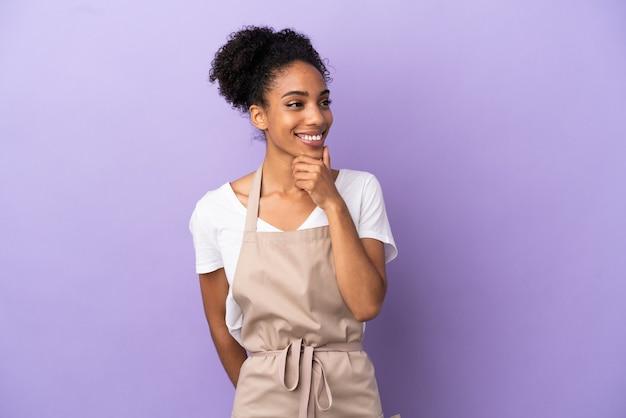 Kelnerka w restauracji latynoska kobieta na białym tle na fioletowym tle, patrząc w bok i uśmiechnięta