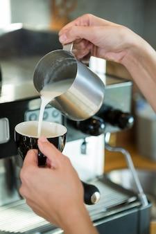 Kelnerka wlewając mleko do kubka