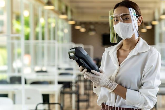 Kelnerka z maską na twarz posiada czytnik kart kredytowych.