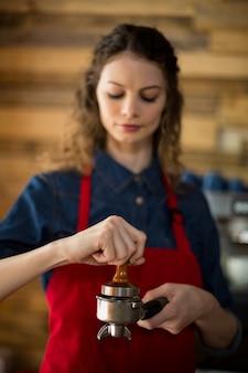 Kelnerka za pomocą sabotażu wciska zmieloną kawę do filtra