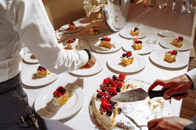 Kelnerzy restauracji kroją słodkie ciasto na kawałki, aby służyć gościom na wakacjach. ręce z bliska widok.