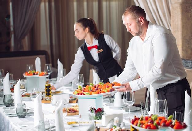 Kelnerzy serwujący stolik w restauracji przygotowujący się do przyjęcia gości.