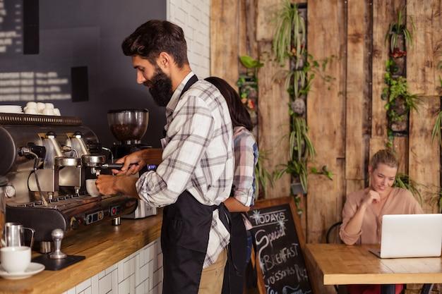 Kelnerzy za pomocą ekspresu do kawy i klienta na laptopie