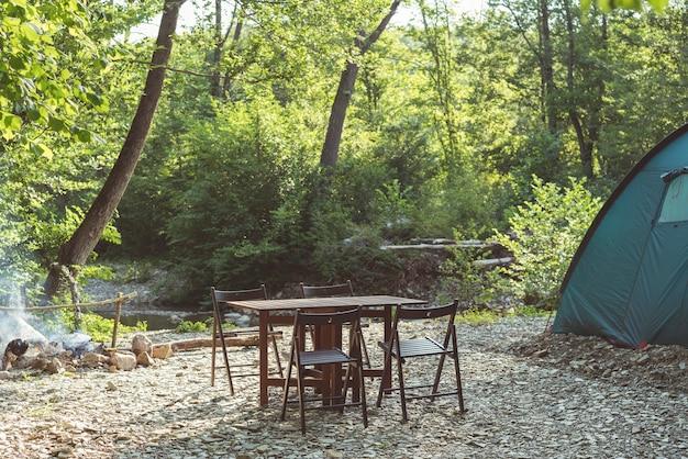 Kemping na plaży górskiej rzeki niebieski namiot obóz stół i krzesła w lesie