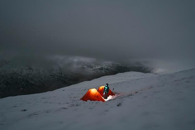 Kemping na zamglonym, zaśnieżonym szczycie góry