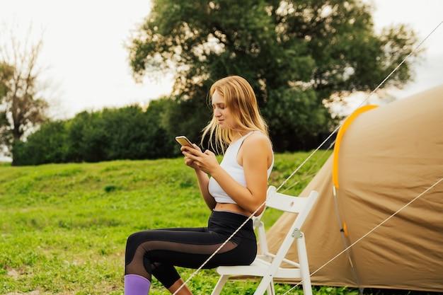 Kemping nad jeziorem. kobieta siedzi na białym krześle w pobliżu namiotu i komunikuje się za pomocą telefonu komórkowego podczas biwakowania. kobieta korzystająca z wakacji przed namiotem kempingowym.