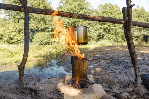 Kemping, nad ogniskiem gotuje się garnek wody.