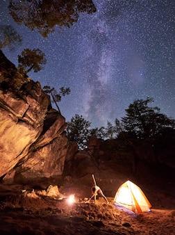 Kemping nocą pośród wielkich stromych formacji skalnych. sportowa szczupła dziewczyna robi rozciągających gimnastycznych ćwiczeniach przy małym turystycznym namiotem na jasnym ciemnym gwiaździstym nieba tle