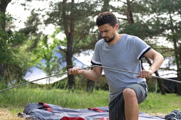 Kemping, podróże, turystyka, koncepcja wędrówki - młody człowiek zakładający namiot na zewnątrz.
