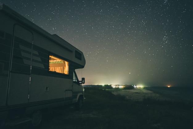 Kemping z kamperem nad morzem. nocna sceneria.
