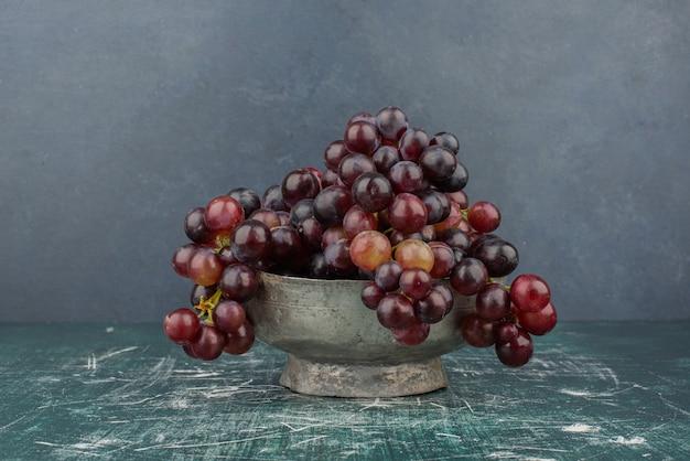 Kępa czarnych winogron w wazonie na marmurowym stole.