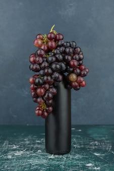 Kępka czarnych winogron wokół butelki na marmurowym stole.