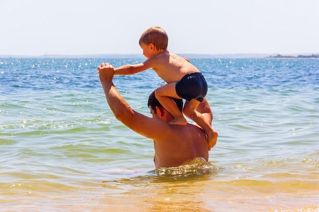 Kercz, rosja - 12 sierpnia 2019: tata i syn bawią się nad morzem w letni dzień