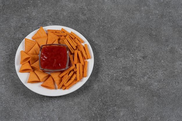 Ketchup, chipsy kukurydziane i suszony chleb na talerzu na marmurowej powierzchni