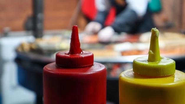 Ketchup i majonez w plastikowych rurkach w pobliżu grilla ulicznego na pierwszym planie z selektywnym fokusem. grill, festiwal ulicznego jedzenia. dwie puszki sosów mięsnych. czerwony i żółty pojemnik.