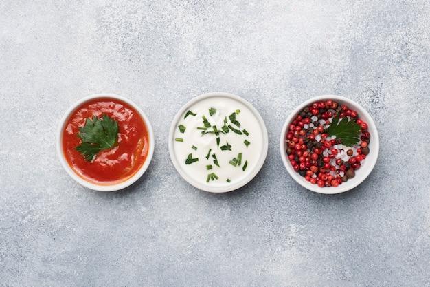 Ketchup majonez zielony przyprawy pieprz sól w talerzach na szarym betonowym stole z miejsca kopiowania.
