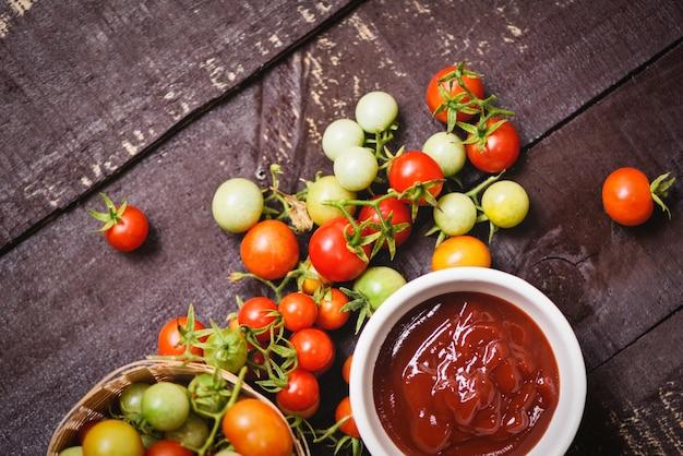 Ketchup w filiżance i świeżych pomidorach na koszykowym pomidorowym kumberlandzie na drewnianym tle