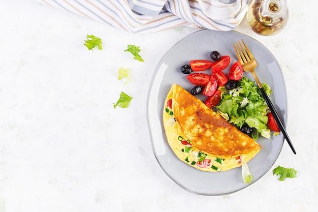 Keto śniadanie. omlet z serem, pomidorami i zieloną cebulką na jasnym stole. włoska frittata. keto, ketogeniczny lunch. widok z góry, nad głową, kopia przestrzeń