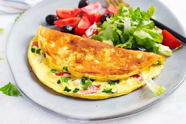 Keto śniadanie. omlet z serem, pomidorami i zieloną cebulką na jasnym stole. włoska frittata. keto, ketogeniczny lunch.