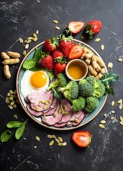 Ketogeniczna dieta niskowęglowodanowa koncepcja widok z góry talerz na kamiennym czarnym tle z żywnością ketonową