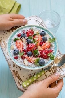 Ketogeniczna dieta paleo o niskiej zawartości węglowodanów, a nie owsianka owsiana. kokosowy budyń chia z jagodami, pestkami granatu i migdałami