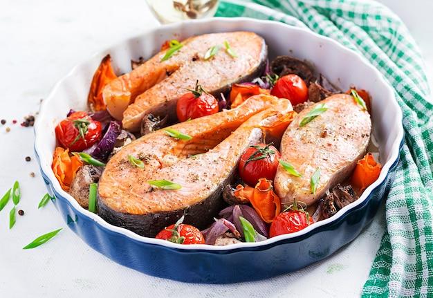 Ketogeniczna kolacja. pieczony stek rybny z łososia z pomidorami, grzybami i czerwoną cebulą. menu diety keto / paleo.