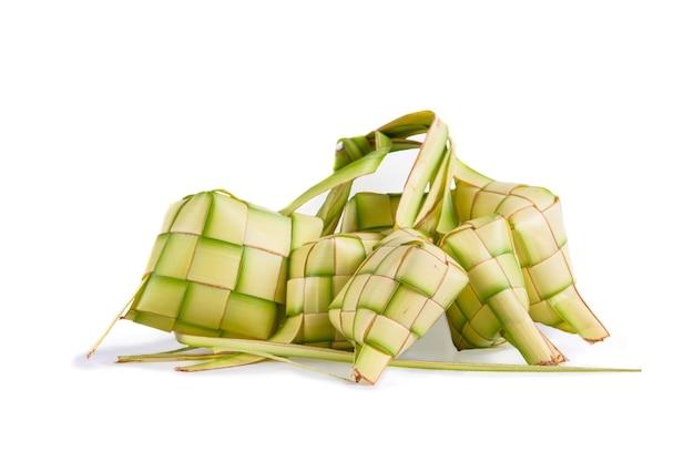 Ketupat na białym tle. typowe danie z ryżu zawiniętego w papierki z plecionych młodych liści kokosa.