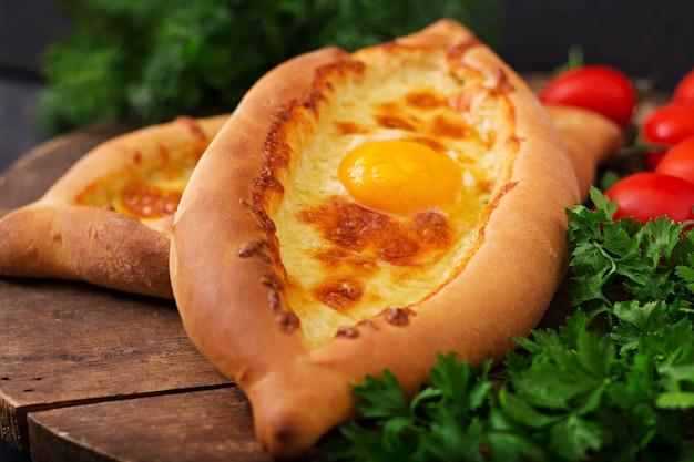 Khachapuri po adjariańsku. otwarte ciasto z mozzarellą i jajkiem. kuchnia gruzińska.