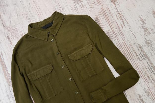 Khaki koszula na drewnianym tle. modna koncepcja