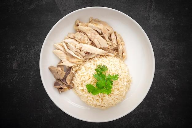 Khao mun gai, tajskie jedzenie, ryż na parze z rosół z kurczakiem, zupą i sosem na ciemnym tle tekstury, widok z góry