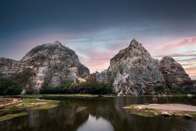 Khao ngu stone park, wapienna góra nad jeziorem i kolorowe niebo o zachodzie słońca w ratchaburi, tajlandia
