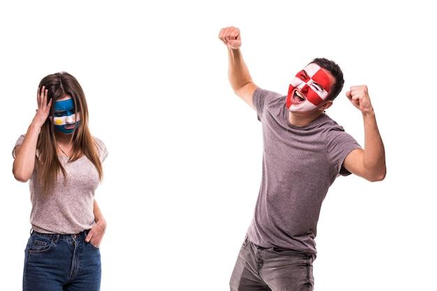 Kibic chorwacji świętuje zwycięstwo nad zdenerwowanym kibicem argentyny z pomalowaną twarzą
