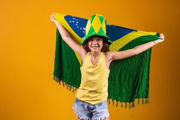 Kibic piłki nożnej, drużyna brazylii. piękna mała dziewczynka kibicuje swojej drużynie na żółtym tle
