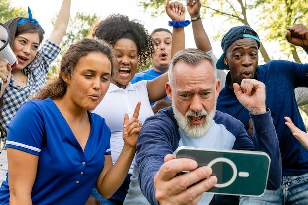Kibice obserwujący, jak ich drużyna wygrywa mecz na telefonie komórkowym