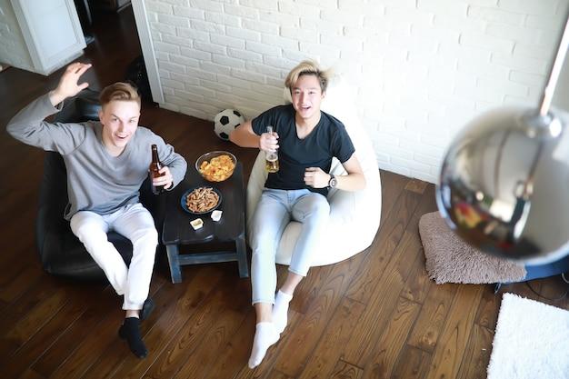 Kibice oglądają mecz i piją piwo pod dachem