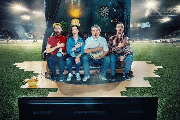 Kibice piłki nożnej siedzący na kanapie i oglądający telewizję na środku boiska do piłki nożnej