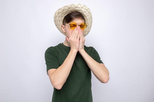 Kichanie chwycił nos młody przystojny facet w okularach z kapeluszem