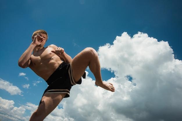 Kickboxer kopie latem na otwartym powietrzu na tle morza.