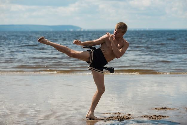 Kickboxer kopie na otwartym powietrzu w lecie na tle morza.
