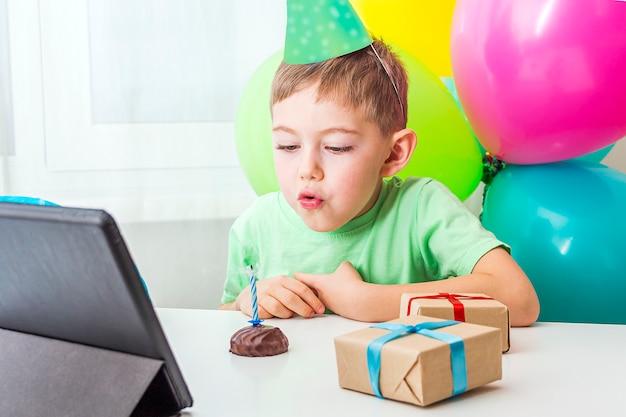 Kid boy obchodzi urodziny online z przyjacielem lub dziadkami podczas rozmowy wideo