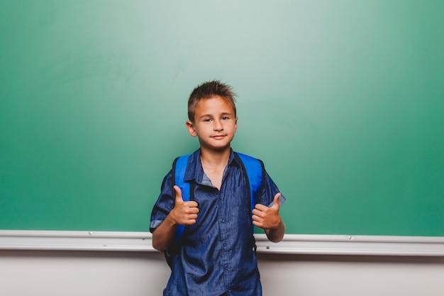 Kid gestykuluje kciuki w klasie