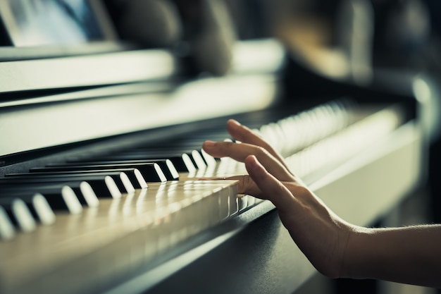 Kid hand playing music keyboard closed up